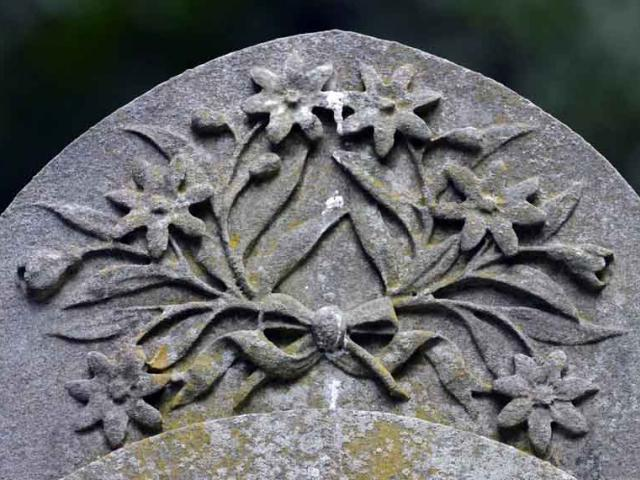 A flowers and bow design on a headstone, carved from Italian marble. The headstone would have...