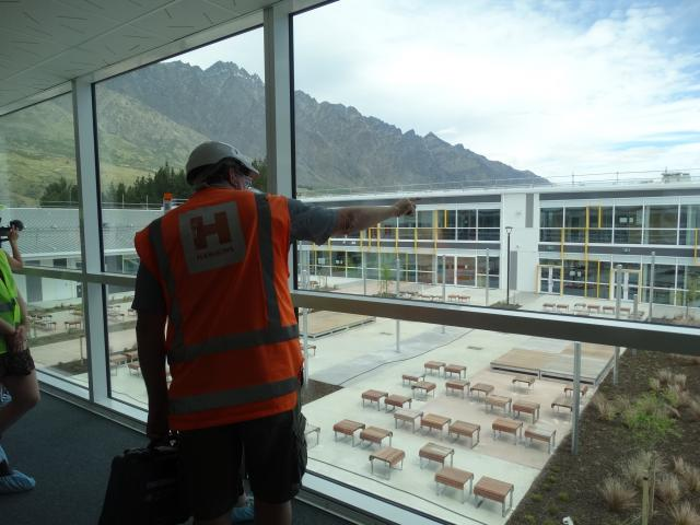 Project manager Blair Grier  points to the other side of the school above the building's internal...