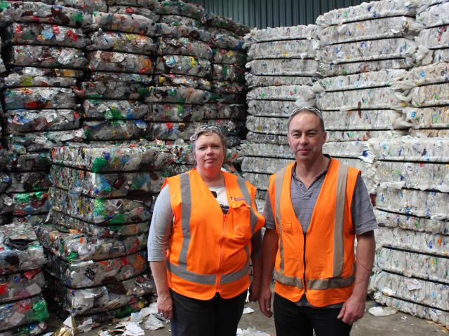 Catherine Gledhill and Jeff Gamble at the recycling plant in Green Island, with baled plastics...