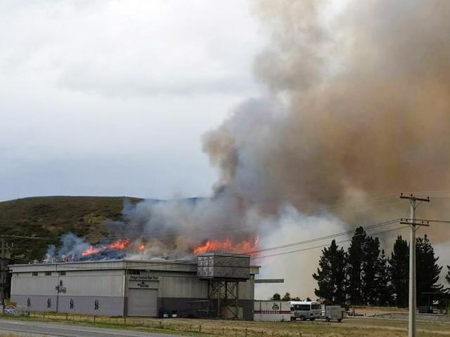 Fire burns on a hillside behind a building at the western end of the Otago Central Rail Trail...