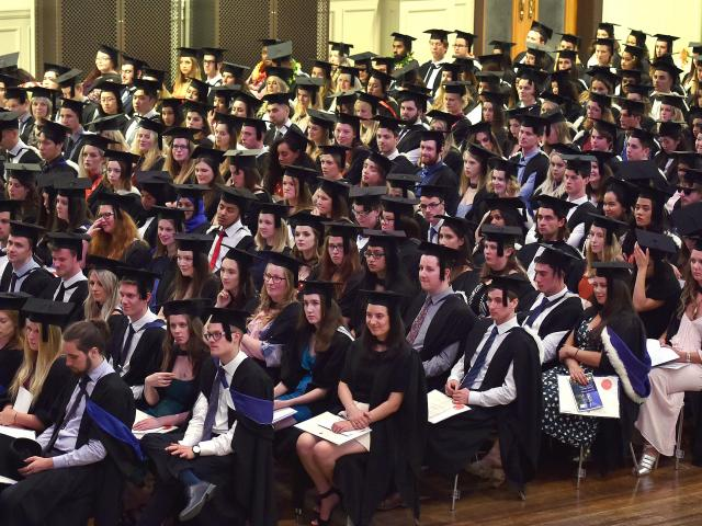 University of Otago graduates, mainly in science, listen to proceedings at the Dunedin Town Hall...