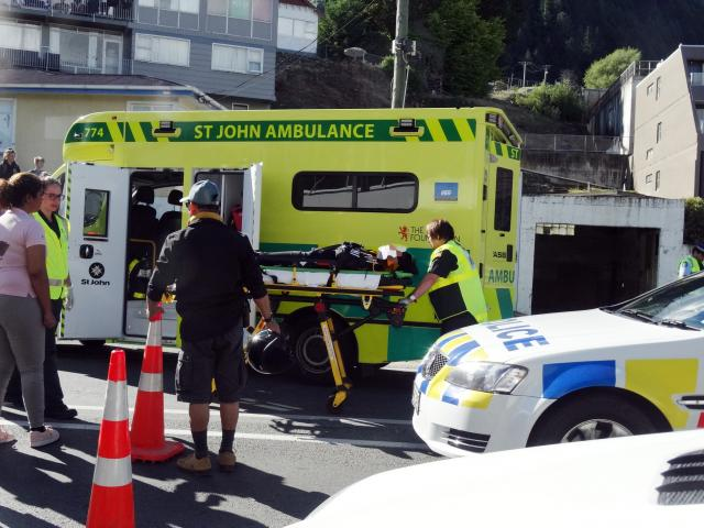 A woman is stretchered to a waiting ambulance after coming off a hired scooter in Shotover St...
