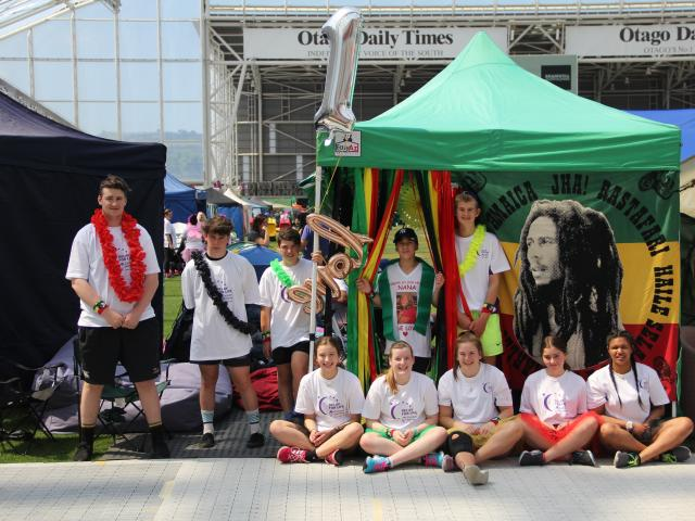 Members of the One Love Relay for Life team relax at their tent site, which had a Bob Marley...