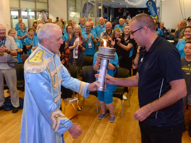 Dunedin's sports liaison  co-ordinator Geoff Simons (left) hands over the Masters Games ...