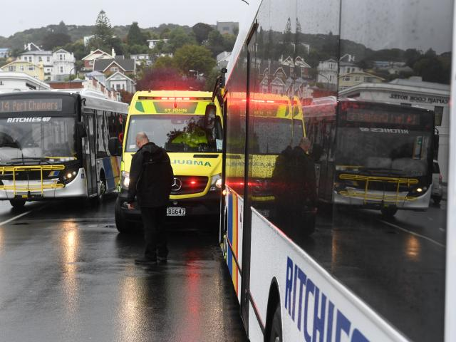 A pedestrian is treated in an ambulance after being hit by a wing mirror on this bus in Albany...