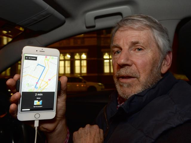Ready to go ... Uber driver Mike Collett waits for his next fare on his phone after the San...