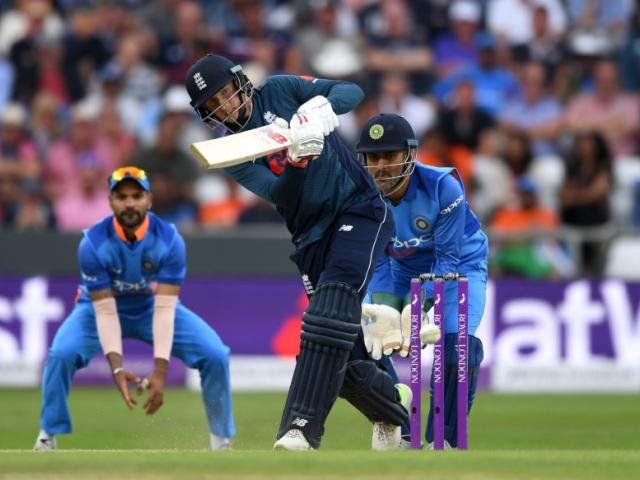 Joe Root plays a shot during his century against India as Virat Kohli and MS Dhoni watch on....