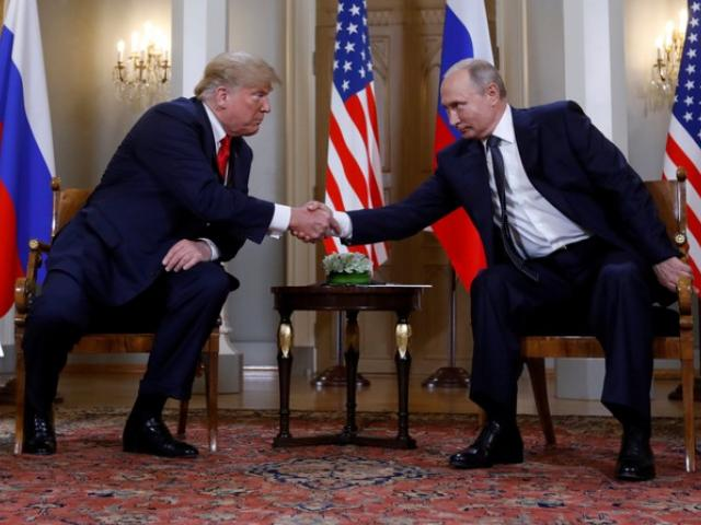 US President Donald Trump and Russia's President Vladimir Putin shake hands as they meet in...