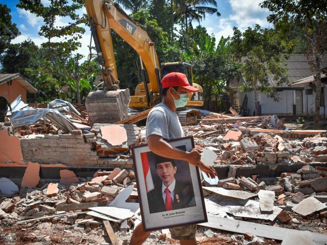 A man carries a picture of Indonesian President Joko Widodo from a school damaged by the August 5...