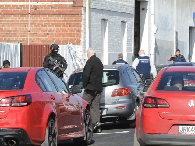 Police surround a warehouse in South Dunedin. Photo: Gerard O'Brien