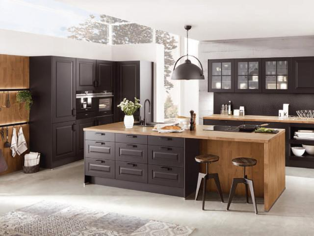 Dark cabinetry offset by natural materials and accessories introduces a country feel to a modern...