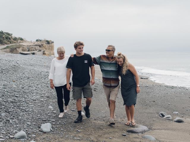 James Arscott walks along a Timaru beach with his family, (from left), Michael and Kate, a...