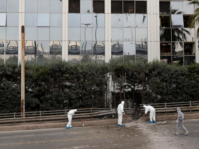 Forensic experts search for evidence after a bomb blast outside SKAI TV building in Athens. Photo...