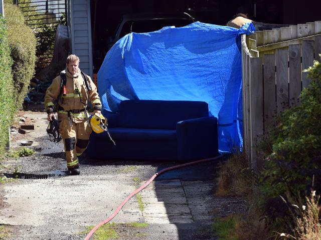 A Fire and Emergency officer at the scene where the car was alight. Photo: Peter McIntosh