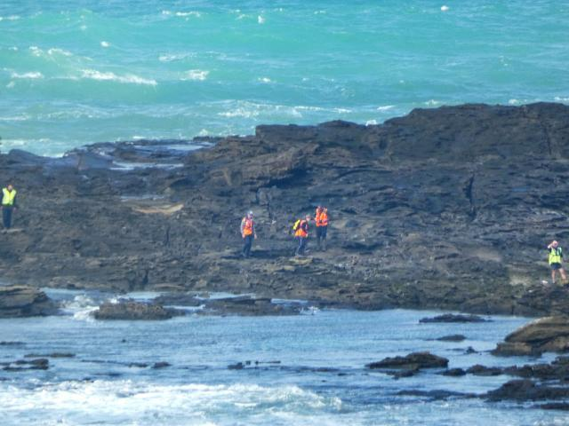Searchers scour the rocks at Slope Point late last month. Photo: Ben Waterworth