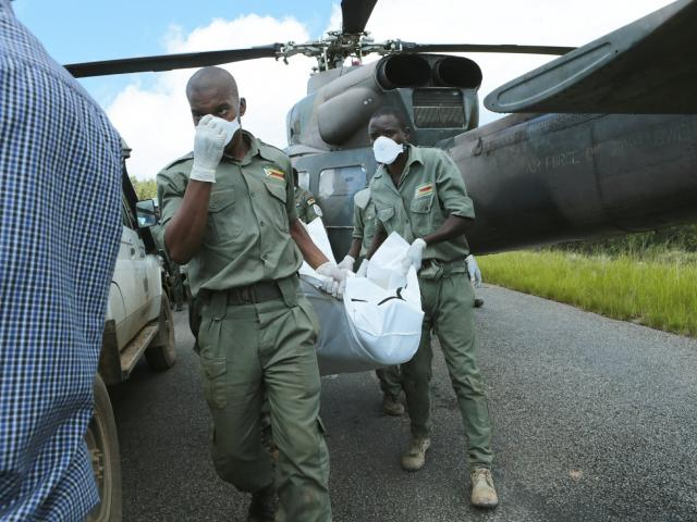 Rescuers carry a body from a military helicopter in Chimanimani, about 600km south east of Harare...