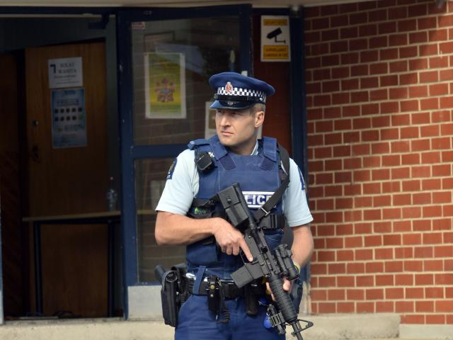 An armed police officer guards the AlHuda Mosque in Dunedin this afternoon following the...