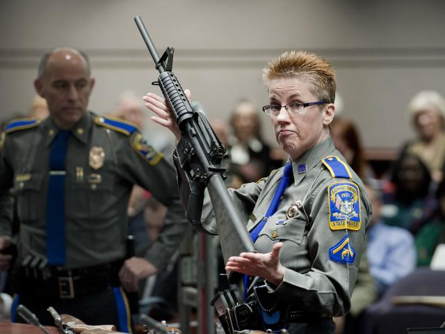 Detective Barbara J. Mattson, of the Connecticut State Police, holds a Bushmaster AR-15 rifle,...
