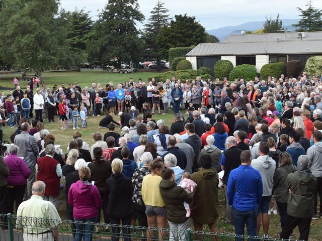 Mosgiel woman Chantelle Carran places flowers on the grass of Memorial Park during a vigil for...
