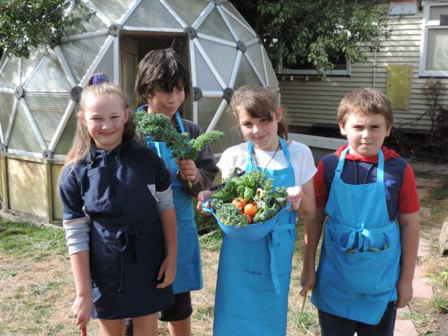 Proudly displaying produce harvested from the school garden for their Garden to Table session are...