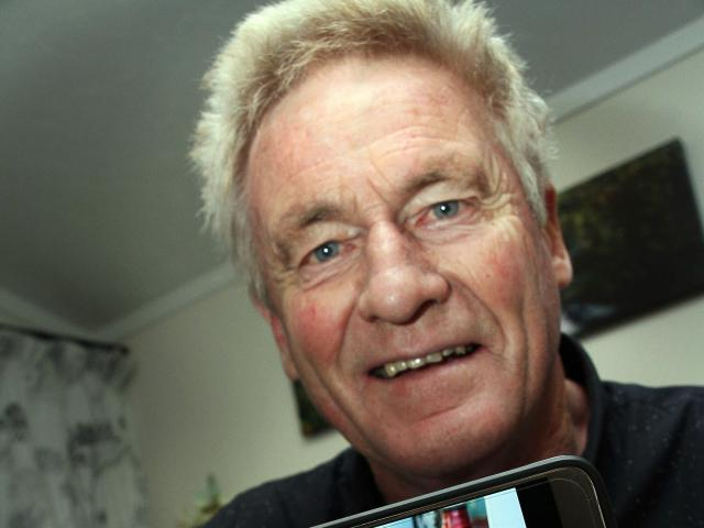Heart-transplant recipient Alastair Gilchrist displays a photo of his daughter, Anna Milne, whose...