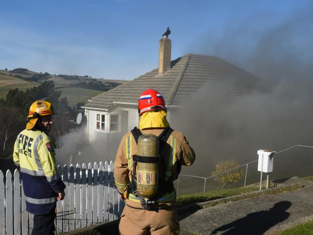 Smoke billows from a home in Puketai St, Andersons Bay, yesterday after a compost pile containing...