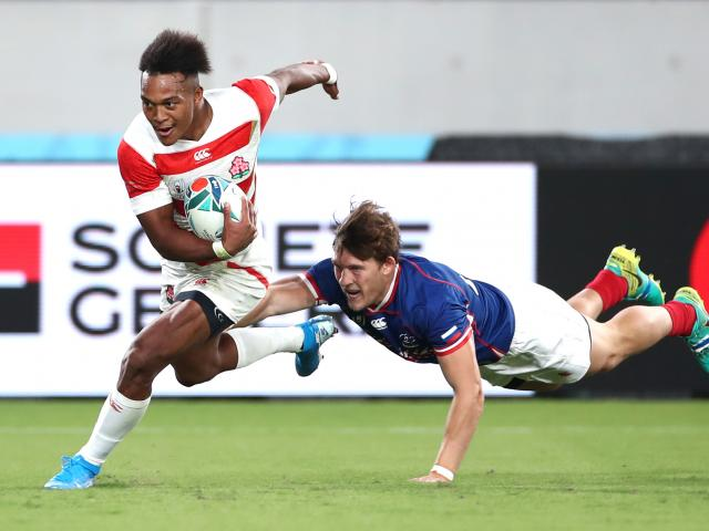 Hat-trick hero Kotaro Matsushima of Japan glides past a Russian defender on his way to the try...
