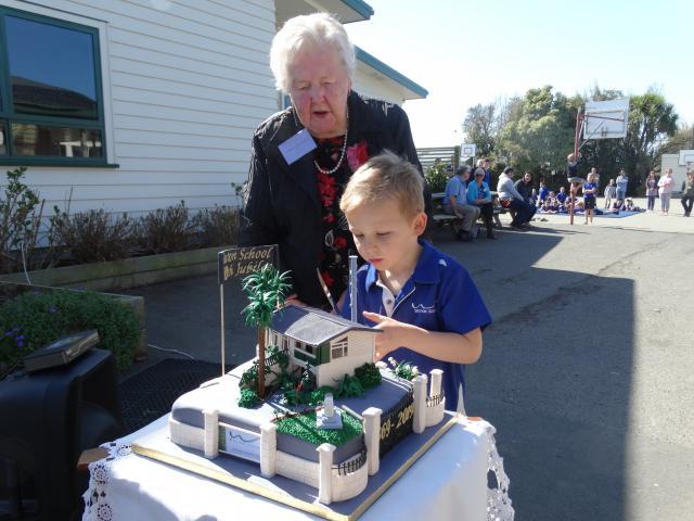Former Weston School pupil Joan Martin (90) and pupil Hugh Newton (5) cut a cake at the school's...