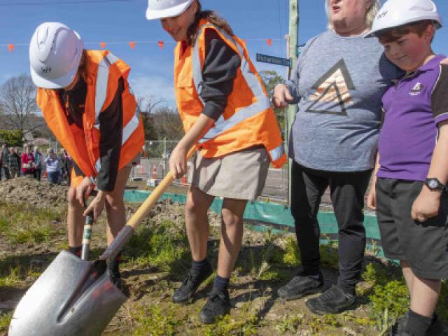 Children from Opawa School turn over the first sod at the new Opawa Library site, its...