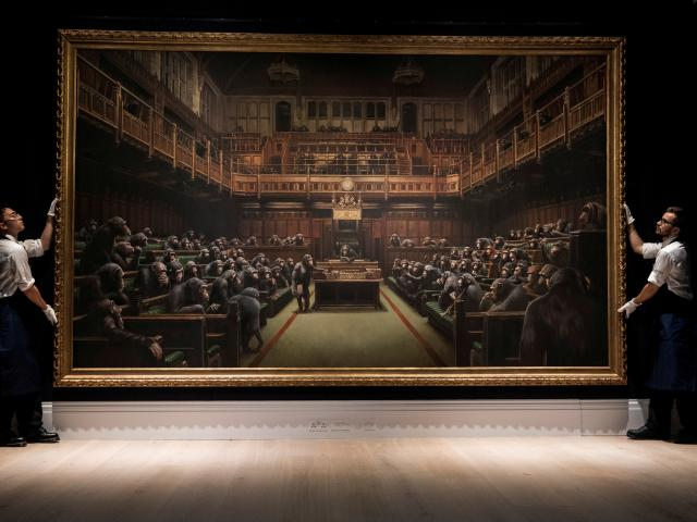 Sotheby's staff pose for a photograph with Banksy's 'Devolved Parliament'. Photo: Reuters