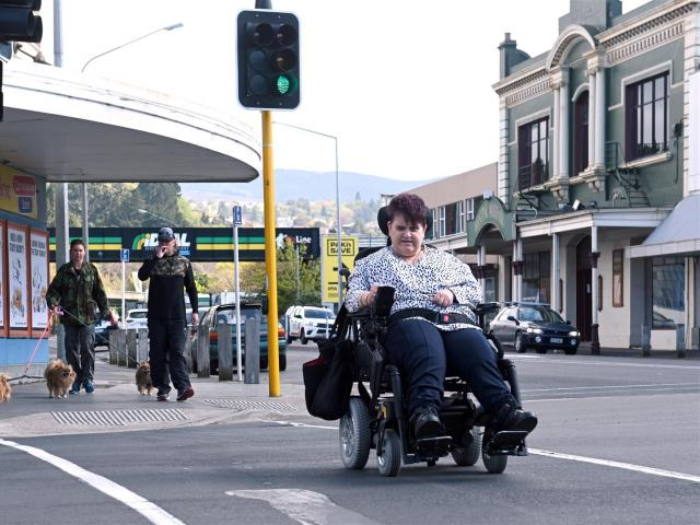 Wheelchair user Fiona Russell safely negotiates the crossing at Cargill's Corner in South Dunedin...