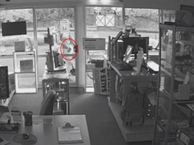 The offender was seen pulling an axe out of his pants before smashing the store door. Photo: CCTV