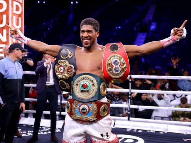 Anthony Joshua celebrates after regaining four of the world heavyweight championship belts...
