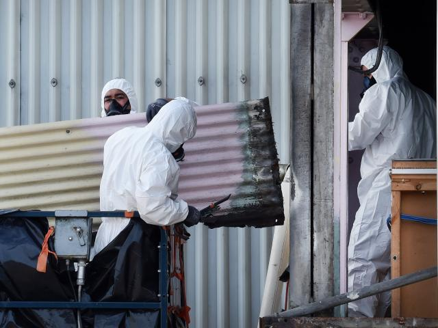 Contractors wearing protective clothing and breathing apparatus remove cladding from the Hillside...