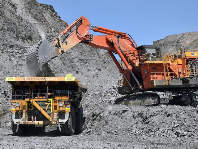 An ore spotter (left) guides the excavator scooping rock in its 40-tonne bucket in the Coronation...