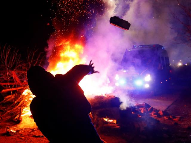 A demonstrator hurls an object towards a police van during a protest in the village of Novi...