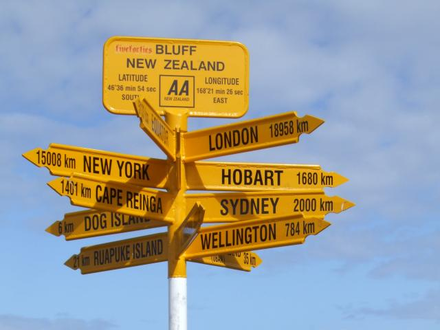 Bluff's iconic Stirling Point sign showing incorrect directions and distances to cities around...