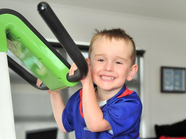 Harry Finch works on strengthening his legs on a vibration plate, as he prepares to start school...