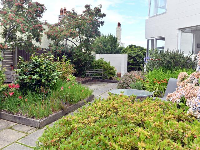 Mature rhododendrons, hydrangeas and roses feature in the shared garden. Mrs Angelo-Roxborough...
