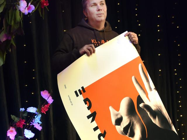 Dunedin Fringe Festival director Gareth McMillan rolls up a poster for the cancelled festival....