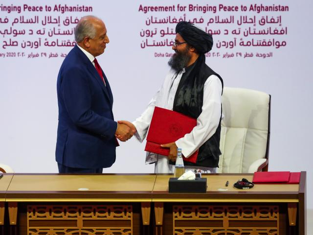 Mullah Abdul Ghani Baradar, the leader of the Taliban delegation, and Zalmay Khalilzad, U.S....