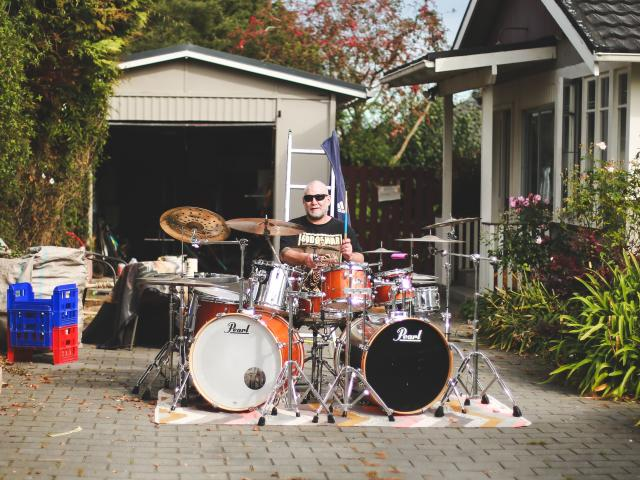 Oamaru musician Tony McDermott on the drums from the comfort of his Arun St driveway