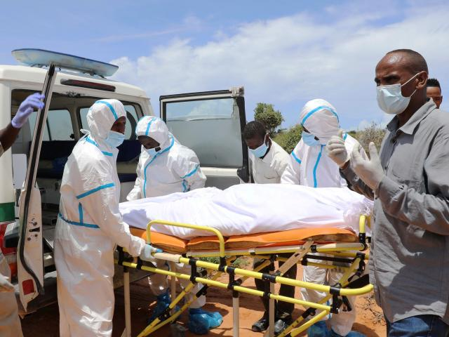 Somali workers in protective suits and civilians prepare to carry the body of a man suspected to...
