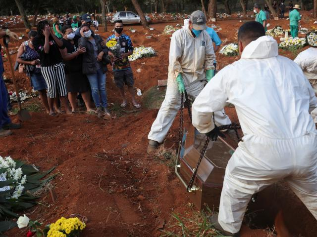 Relatives react during the burial of Geraldo Magalhaes, who died from the coronavirus disease....