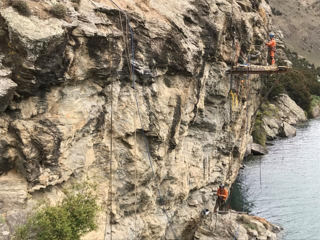 Workers pay attention to an area of cliff face in the Reilly Bluff during construction of the...