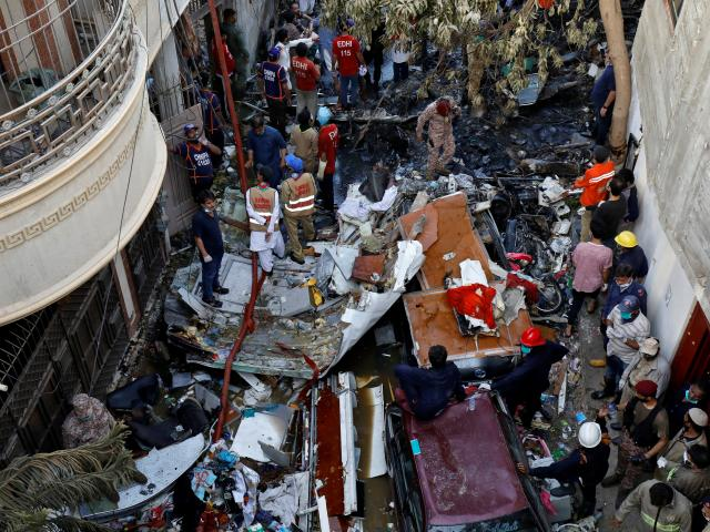 Rescue workers gather at the site of a passenger plane crash in a residential area near an...