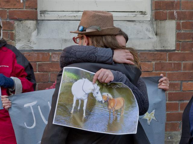Mandy Mayhem-Bullock (right) looks on as her husband, Lee, is embraced by a supporter after...