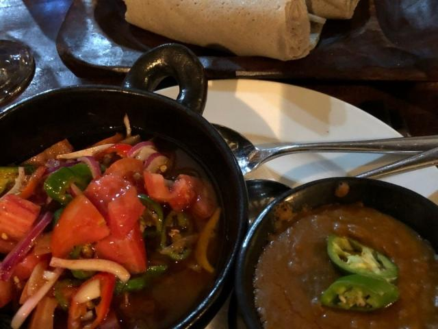 A lentil stew, tomato and red onion salad and rolled injera.