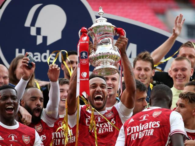 Arsenal skipper Pierre-Emerick Aubameyang lifts the trophy as his teammates celebrate after...
