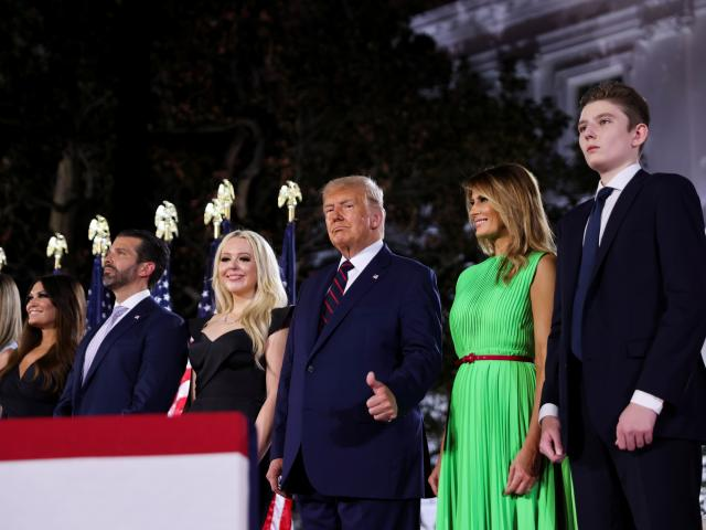 President Donald Trump gives a thumbs-ups next to first lady Melania Trump and their extended...
